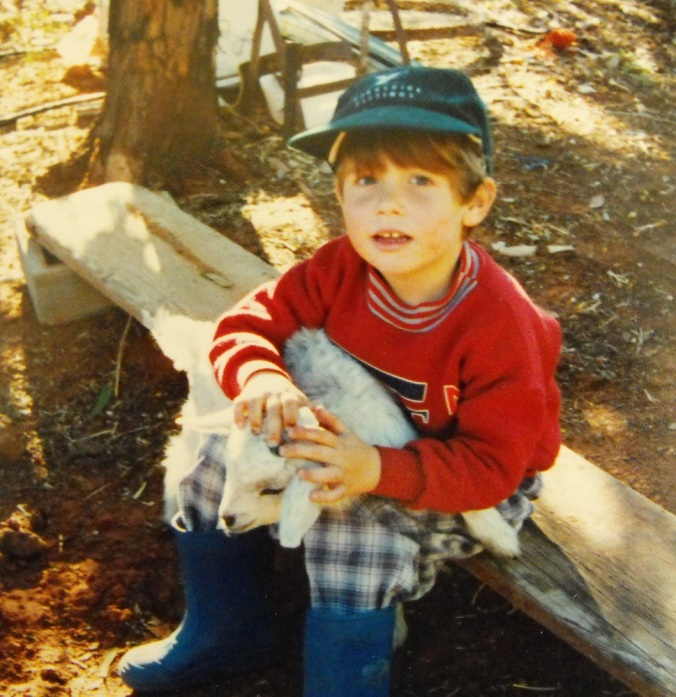 boy-holding-goat-outback
